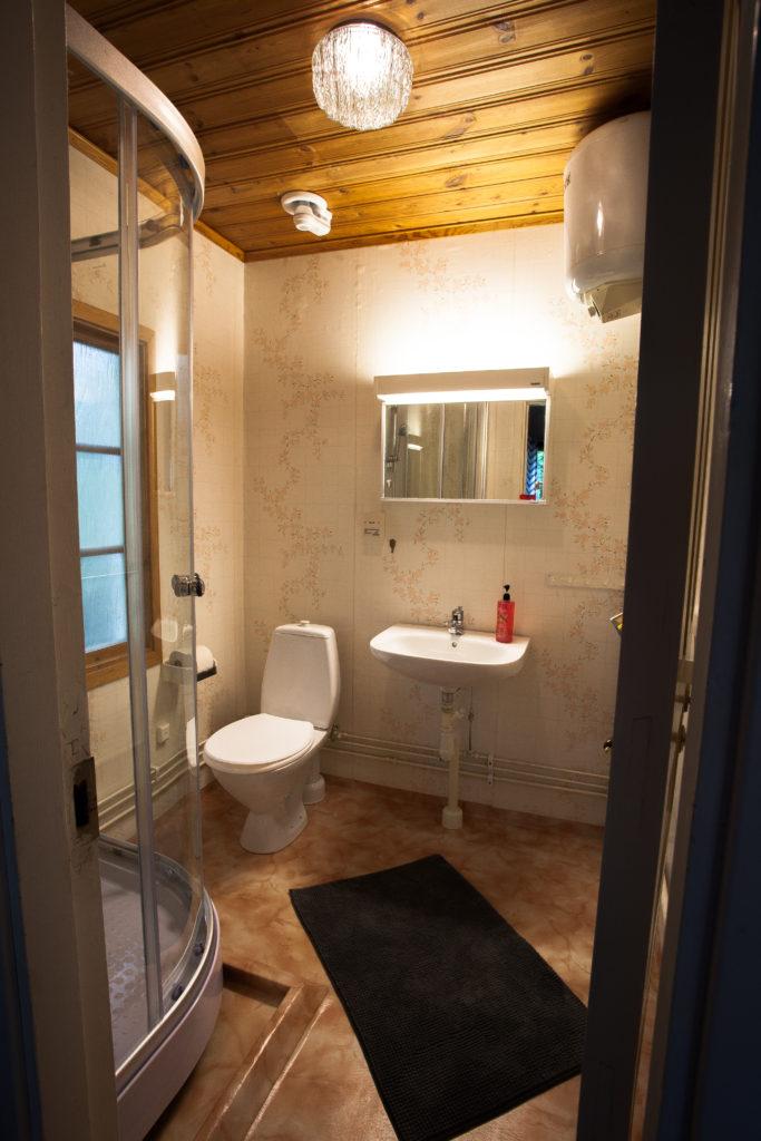Äldre men funktionsdugligt badrum med duschkabin.