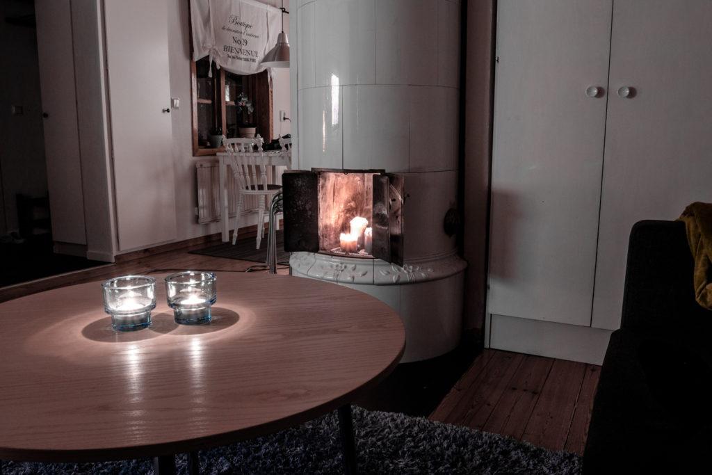 Mys i vardagsrummet med ljus i kakelugnen.